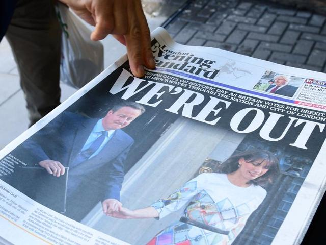 A man takes a copy of the London Evening Standard on Friday with the front page reporting the resignation of British Prime Minister David Cameron and the vote to leave the EU in a referendum.