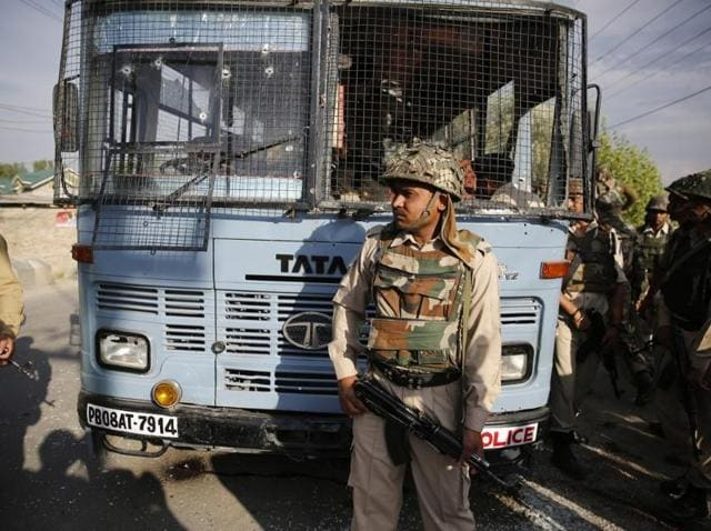 Security personnel stand guard near a damaged bus that was attacked by militants in Pampore, on the outskirts of Srinagar.