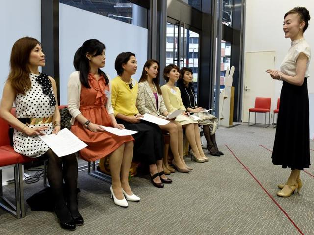 Japan High Heel Association's managing director Madame Yumiko (R) giving a lesson on high heels in Tokyo.