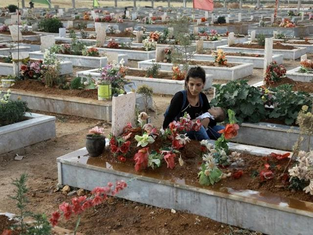 A Syrian Kurdish woman mourns next to the grave of a relative at a cemetery in the Syrian Kurdish town of Kobane (aka Ain al-Arab) on June 24, 2016.