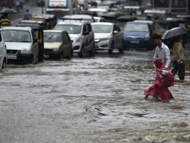 People wade through a waterlogged road in LBS Marg near Ghatkopar on Saturday.