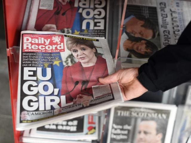 A man takes a copy of the Daily Record newspaper reporting on the pro-Brexit result of the UK's EU referendum vote and with an image of Scotland's First Minister, Nicola Sturgeon.