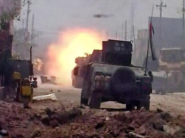 This image made from Associated Press video shows Iraqi troops carry an Iraqi flag on their tanks after a senior Iraqi commander declared that the city of Fallujah was