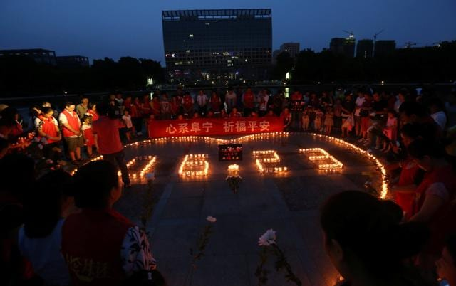 People pray for victims of the tornado which hit Yancheng on Thursday, at a square in Ningbo, Zhejiang province, China on Sunday.