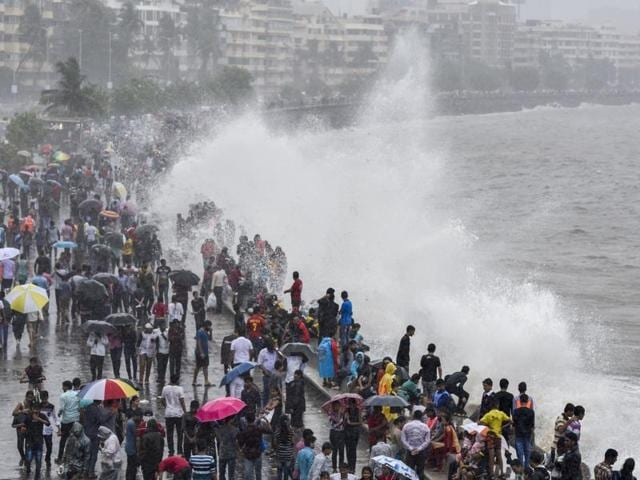 People enjoy the high tide at Marine Drive on Sunday.