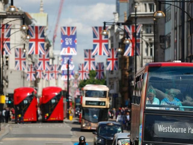 Buses travel along Oxford Street underneath Union flags in central London.