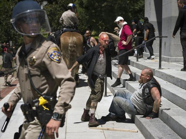 A wounded man stands by another wounded man sitting on the steps of the California state Capitol after members of right-wing extremists groups holding a rally outside the state Capitol building clashed with counter-protesters in Sacramento, Calif., Sunday, June 26, 2016.