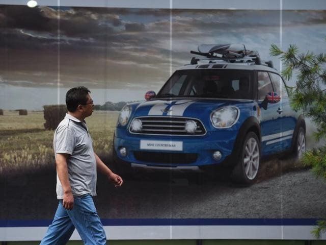 A woman walks past a Mini showroom in Beijing on Monday. Britain's vote to leave the European Union has added new uncertainties to the world economy at a time when downward pressures on China's economy are mounting, Premier Li Keqiang said at a World Economic Forum meeting in Tianjin.