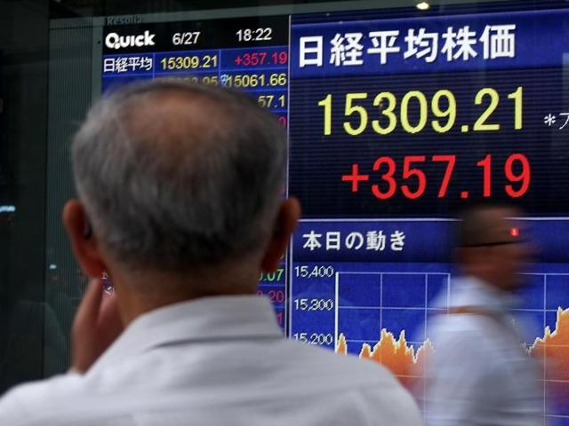 A pedestrian looks at a share prices board showing numbers from the Tokyo Stock Exchange in Tokyo on June 27, 2016.