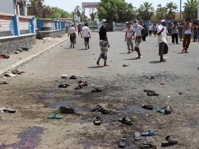 People walk at the site of a suicide bombing in the southern port city of Aden.