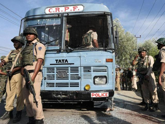 Security forces inspect a CRPF bus attacked by militants on the Srinagar-Jammu national highway in Pampore on Saturday.