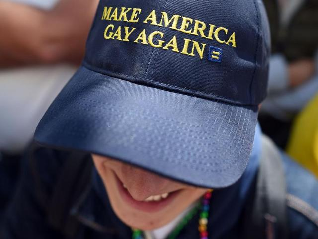A man wearing a Donald Trump inspired hat watches the San Francisco Pride parade in San Francisco, California on Sunday.