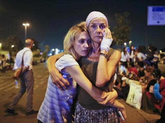 Passengers embrace each other as they wait outside Istanbul's Ataturk airport, early Wednesday, June 29, 2016 following their evacuation after a blast.