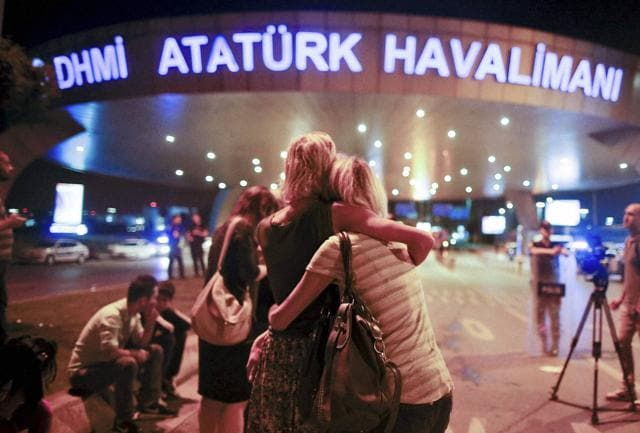 Passengers embrace each other at the entrance to Istanbul's Ataturk airport, early on Wednesday, following their evacuation after a blast. Suspected Islamic State group extremists hit the international terminal of Istanbul's Ataturk airport, killing dozens of people and wounding many others.