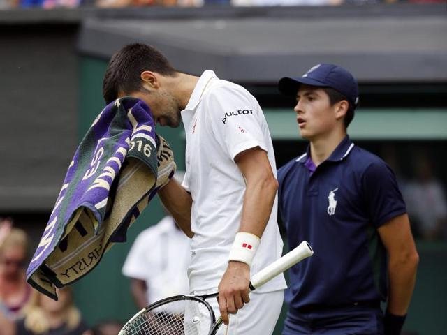 James Ward during his first-round match against Djokovic. The green-and-purple Wimbledon towels can be bought for $35 apiece.