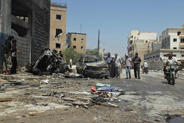 Civilians inspect a site hit by an airstrike in the rebel-controlled city of Idlib, Syria.