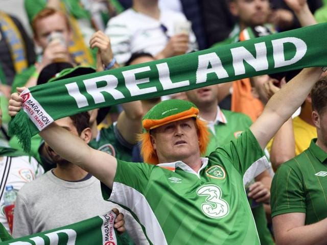 Ireland fans holding stuffed leprechauns with their faces painted in the colours of the Irish flag pose.