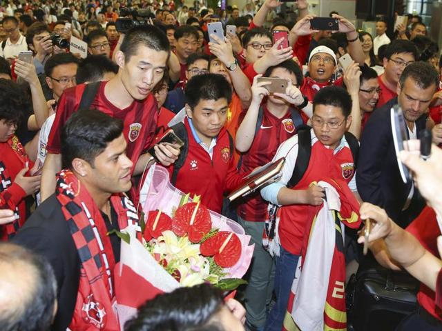 Brazilian football player Hulk (left) is surrounded by excited fans waiting at the airport in Shanghai.
