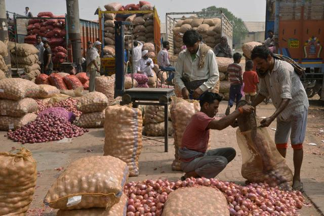 Indian labourers fill sacks with onions after sorting themat a wholesale vegetable and fruit market. Consumer confidence in India declined in the second quarter this year with concerns over fuel prices and rising inflation.