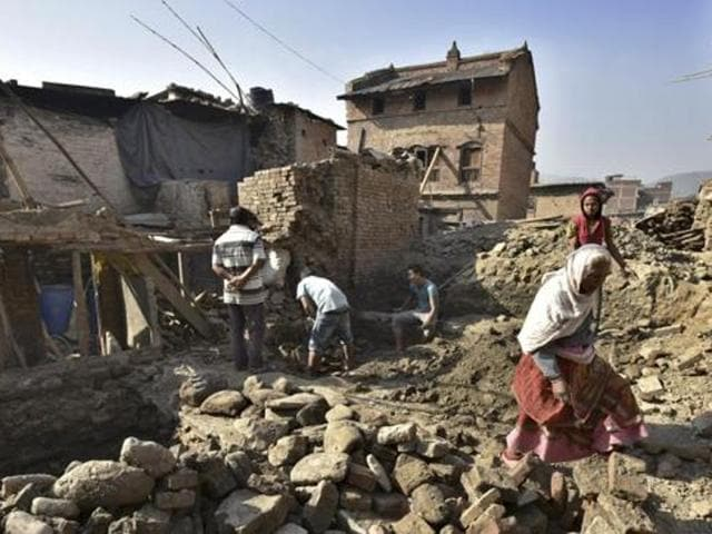 People move through earthquake-damaged houses that continue to be in a bad condition one year after the devastating earthquake in Nepal.