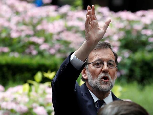 Spanish prime minister Mariano Rajoy waves as he waits for his car at the end of the second day of the EU Summit in Brussels, Belgium.