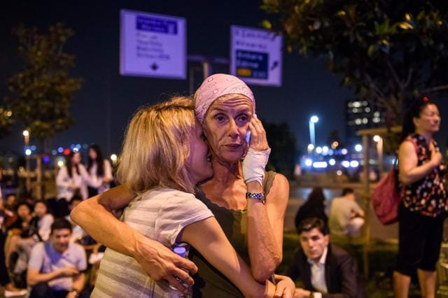 Passengers embrace outside Ataturk airport`s main entrance in Istanbul, on Tuesday.