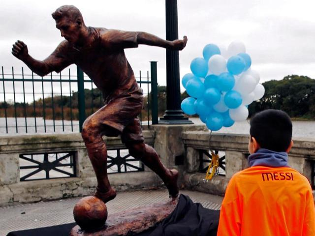 A boy wears a Lionel Messi jersey as he approaches the statue of Argentine football player Messi after it was unveiled in Buenos Aires, Argentina.