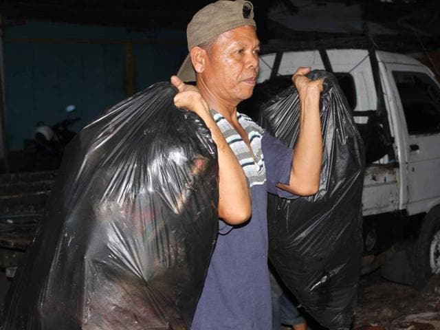 This picture taken on May 18, 2016, shows Indonesian policeman Seladi carrying bags of garbage in Malang, East Java.