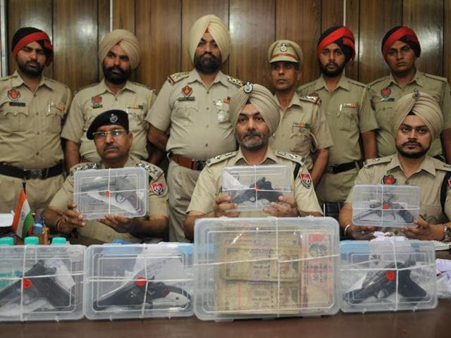 Assistant inspector general HPS Khakh (centre) and other officers showing the seized pistols and cash at a press conference in Jalandhar on Wednesday.