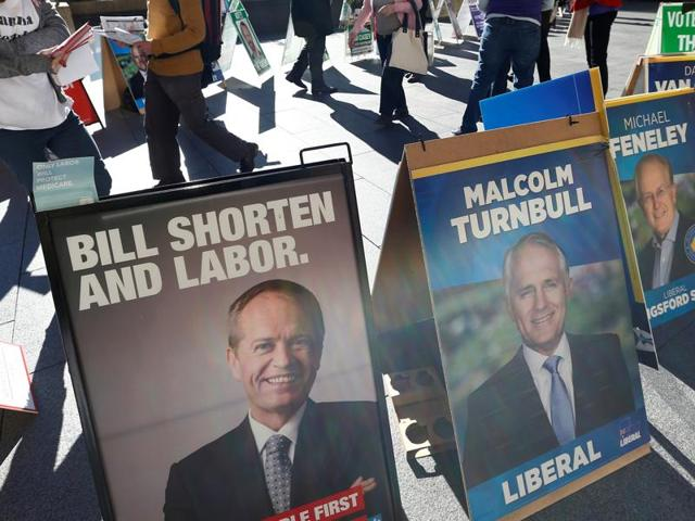 Early voters in Australia's July 2 general election walk to a polling centre past banners promoting Labour leader Bill Shorten (L) and Liberal Party Prime Minister Malcolm Turnbull at Sydney's Town Hall on Wednesday.