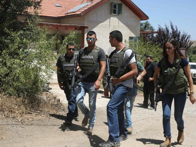 Israeli policemen walk outside a house in the Jewish settlement of Kiryat Arba in the occupied West Bank where a 13-year-old Israeli girl was fatally stabbed in her bedroom.(AFP Photo)