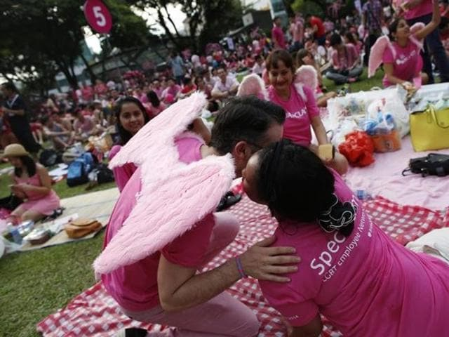 Participants dressed in pink embrace as they enjoy a picnic before taking part in the forming of a giant pink dot at the Speakers' Corner in Hong Lim Park in Singapore.