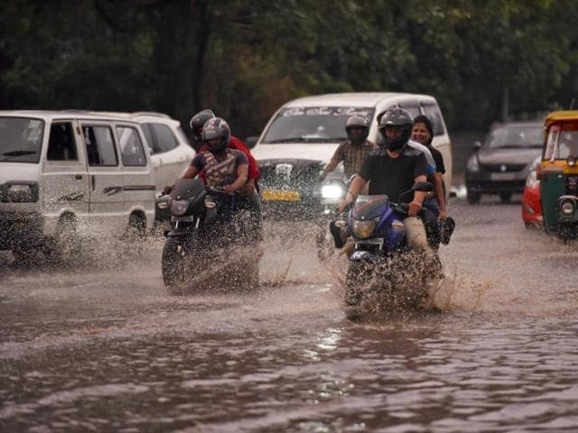 Visitors enjoy the rain at Rajpath in New Delhi on Thursday.