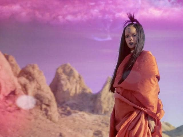 The visual spectacle features a top-knotted Rihanna dressed in an orange sari and adorned with henna on a rocky, alien planet and, towards its conclusion, transforming into a stellar entity.