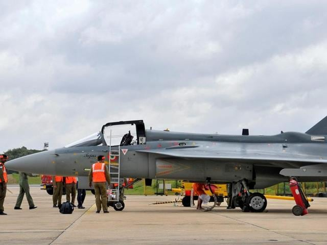 Airport ground staff stand besides Tejas, India's first locally-built Light Combat Aircraft (LCA), before its induction into the Indian Air Force at the Hindustan Aeronautics Limited (HAL) Airport in Bengaluru.