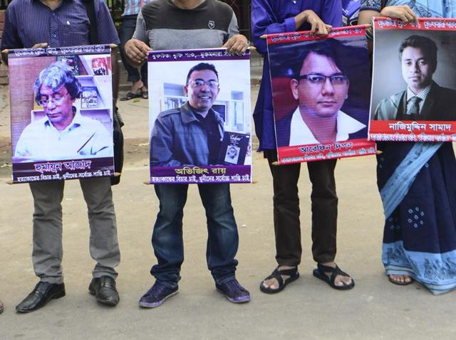 File photo of Bangladeshi activists holding photos of activists, writers and bloggers who were murdered by unidentified assassins in the last few years in Dhaka on June 15.
