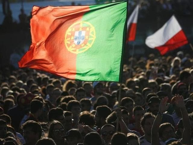 Fans hold Portuguese and Polish flags before they watch the Euro 2016 match.