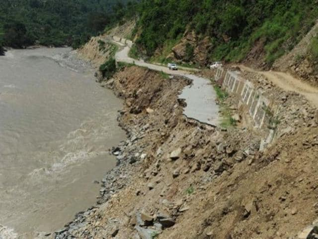 A truck is parked on a stretch of damaged road alongside the Mandakini river near Tilwara, in the flood affected area of Uttarakhand on July 1, 2013.