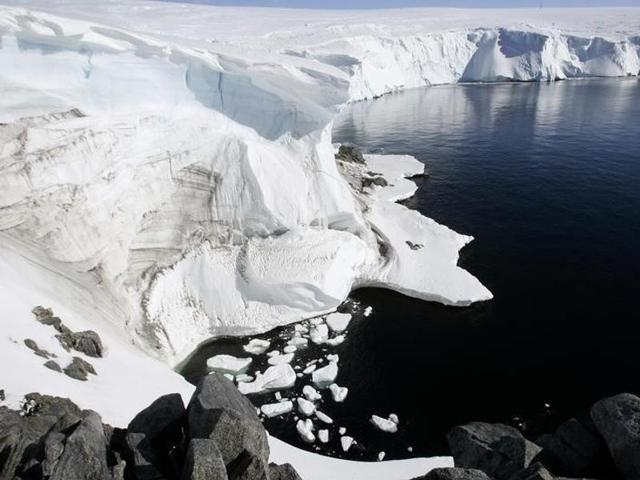 Two Adelie penguins stand atop a block of melting ice on a rocky shoreline at Cape Denison, Commonwealth Bay, in East Antarctica in this January 1, 2010 file photo.