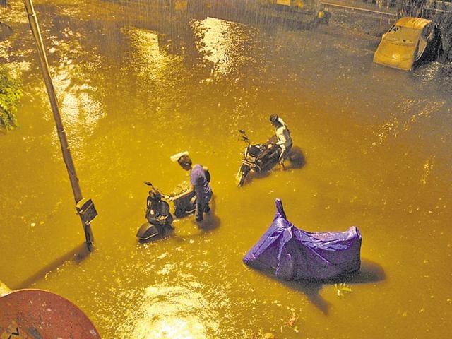 Residents make their way through a waterlogged road near Thane court on Thursday.