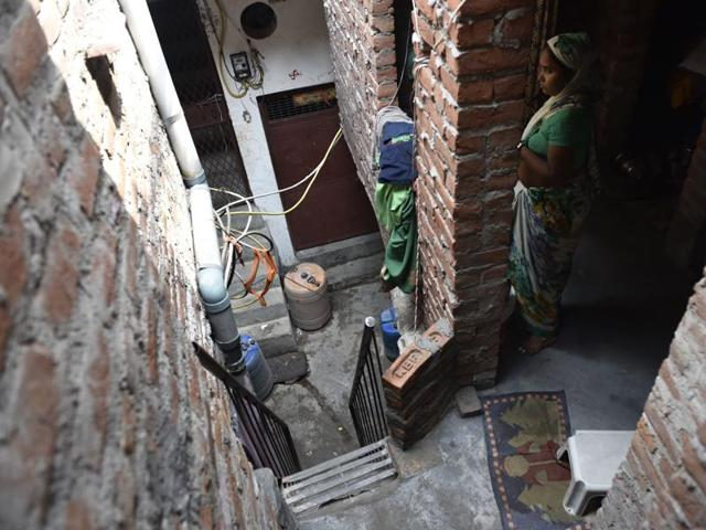 Neighbours peep outside to look at the house where a man killed his wife and daughter and committed suicide in Delhi's Okha on Thursday night.