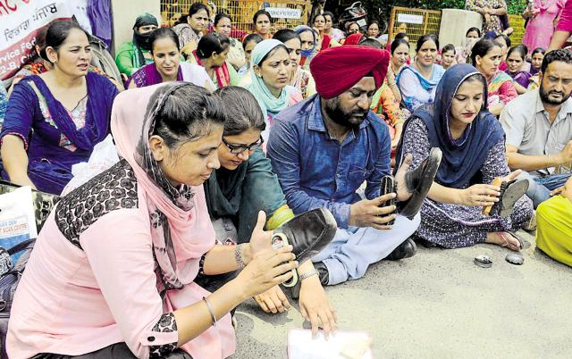 Nurses and paramedical staff polishing shoes during their protest outside the Guru Nanak Dev Hospital in Amritsar on Friday.
