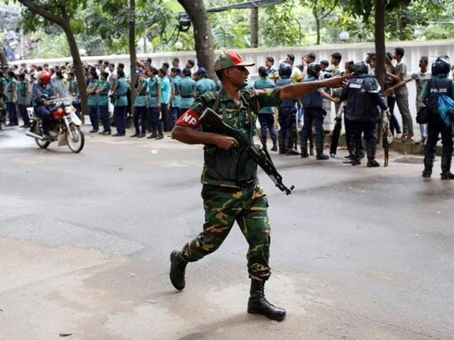 A securityman reacts near the Holey Artisan restaurant after gunmen attacked the upscale cafe in Dhaka.