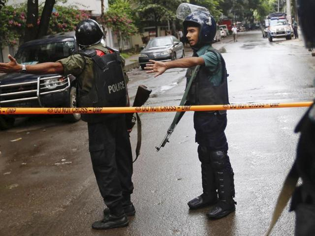 Bangladeshi policemen clear out an area to facilitate action against heavily armed militants who struck at the heart of Bangladesh's diplomatic zone on Friday night.