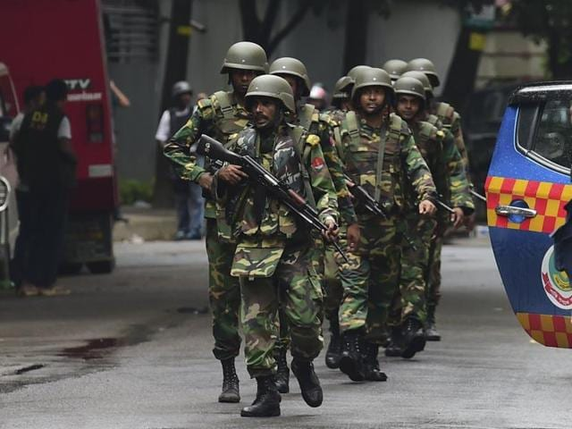 Bangladeshi soldiers patrol a street during a rescue operation as gunmen take position in a restaurant in  Dhaka's high-security diplomatic district.