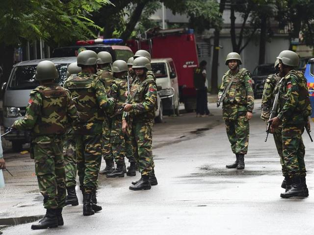 Bangladeshi army soldiers stand guard during a rescue operation as gunmen take position in a restaurant in the Dhaka's high-security diplomatic district on July 2, 2016.