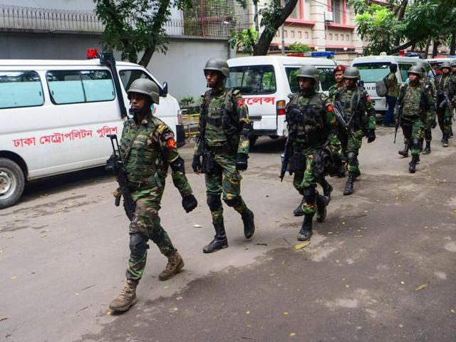 Bangladeshi military commandos walk away from an upscale restaurant after a bloody siege ended in Dhaka on July 2, 2016.