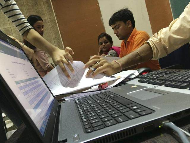 Teachers check the documents of students completing their admission formalities at Venkateshwar college in New Delhi.