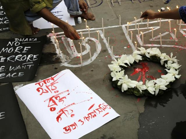Indian activists participate in a candle light vigil protesting the Bangladesh restaurant attack.