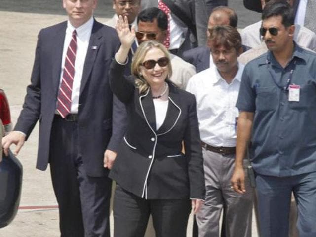 Hillary Clinton, surrounded by Indian security personnel, waves upon her arrival at an airport in Kolkata.